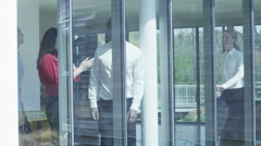 4K Business people talking in modern glass office, view from outside looking in. Stock Footage