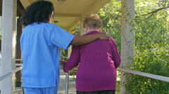 Nurse helping woman with crutches outdoor. Rehab concept Stock Footage