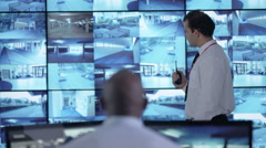 4K Surveillance team watching CCTV screens & reacting to suspicious activity Stock Footage