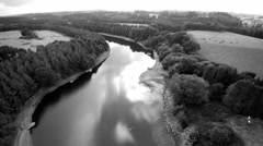 Aerial over a river flowing through hills in countryside. Black and white. 4K Stock Footage