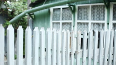 Panorama of an exterior of a single-storey wooden house behind a white fence. HD Stock Footage