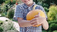 Boy with Pumpkin in Green Garden Stock Footage