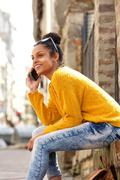 Young woman sitting along a street using mobile phone Stock Photos