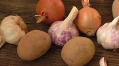 Garlic and onion, potatoes on cutting board Stock Footage