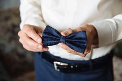 Wedding accessories. Bow tie in the hands of the groom Stock Photos