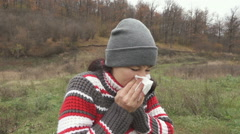 Young beautiful woman stands and sneezes outdoors in autumn cold day. Stock Footage