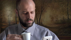 Bald man takes coffee while checking email on mobile Stock Footage