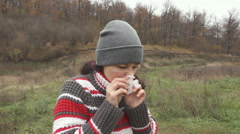 Young beautiful woman stands and sneezes outdoors in autumn cold day. Slow Mo Stock Footage