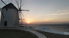 Sun setting behind old windmills on mykonos, greece Stock Footage