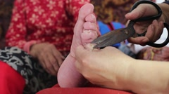 Cutting toenails for a 97 years old foot bound woman, born in 1919 Stock Footage