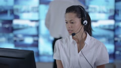 4K Surveillance officer communicating via headset in control room Stock Footage