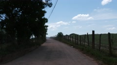 Rural road through green fields in Brazil Stock Footage