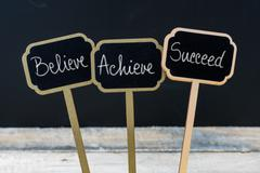 Motivational message Believe, Achieve, Succeed written with chalk Stock Photos
