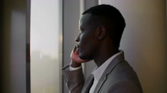 Young black man in suit using smartphone standing by window in ghetto office in Stock Footage