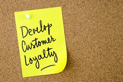 Develop Customer Loyalty text written on yellow paper note Stock Photos