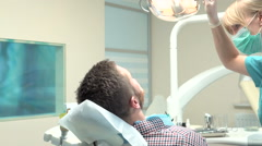 Doctor dentist making an injection of local anesthetic into the gums. Slider. Stock Footage