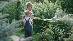 Brother and Sister Helping Watering Garden with Hose Stock Footage