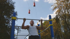 Young athlete doing chin-ups and performs exercises on horizontal bars outdoor Stock Footage