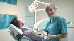 Female dentist drilling tooth, looking to camera. Stock Footage