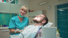 Female dentist examining teeth of male patient, looks to the camera. Slider shot Stock Footage