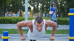 Athletic man doing push ups on bars at sports ground in city park. Stock Footage
