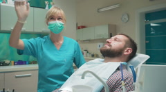 Female dentist sits down and examining teeth of male patient. Stock Footage