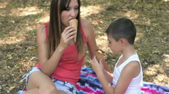A mother with a six year old son eating ice cream in the Park and smiling Stock Footage