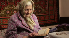 The Elderly Woman Reads Bible Stock Footage