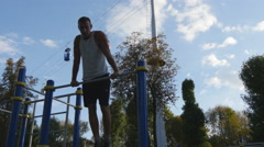 Young athlete doing chin-ups on horizontal bars outdoor. Fitness man training Stock Footage