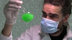 A Laboratory Assistant In A Face Mask Is Shaking A Flask With A Green Liquid Stock Footage