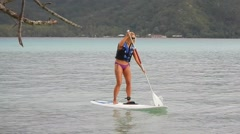 A woman stand up paddle boarding on the South Pacific near Tahiti, French Polyne Stock Footage