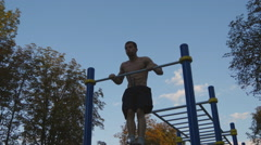 Strong muscular man doing muscle ups in a park. Young athlete doing chin-ups Stock Footage