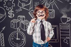 Little boy as businessman or teacher with mustache and glasses standing on dark Stock Photos