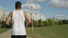 The athlete is running on a racetrack in the park. Back view. Sunny summer day. Stock Footage