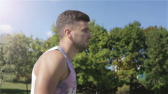 The athlete is walking in the park. Side view. The sun glare in a blue sky. Stock Footage