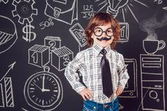 Little boy as businessman or teacher with mustache and glasses standing on a Stock Photos