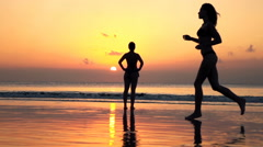 Pretty, young woman in bikini running on the beach during sunset, super slow mot Stock Footage