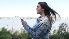 Young millennial beautiful happy busy woman girl outside walking and texting on Stock Footage