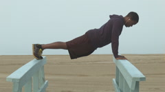 A young man working out and doing push ups on the beach. Stock Footage