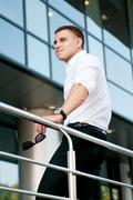 Young man with short hair standing backward near glassy building Stock Photos