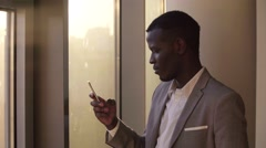 Young black man photographed views and looks at the dirty window in office in a Stock Footage