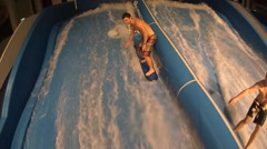 A young man surfing on a indoor wave pool , slow motion. Stock Footage