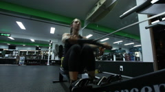 A woman working out and doing the rowing machine at the gym. Stock Footage