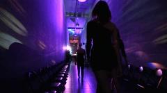 Three girls in tight black dresses go through corridor Stock Footage