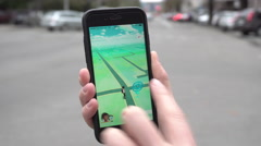 Unidentified Woman Hold a Phone Playing Pokemon Stock Footage