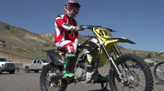 A young man kick starting his motocross dirt motorcycle, super slow motion. Stock Footage