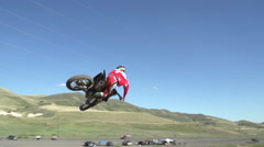 A young man riding a motocross dirt motorcycle off a jump. Stock Footage