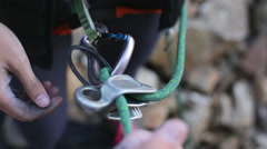 A young man preparing carabiners to go rock climbing. Stock Footage