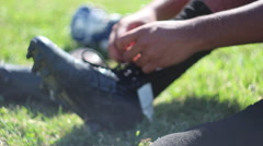 Lacrosse player tying shoes. Stock Footage
