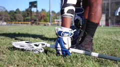 A lacrosse player picking up stick from ground, slow motion. Stock Footage